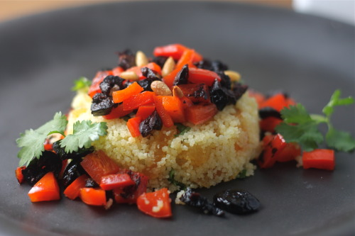theboredvegetarian:  Moroccan Cous Cous with Blackened Red Pepper, Olives, Apricot and Toasted Pine Nuts Last weekend I threw a dinner party at my apartment for six of my lovely friends.  Work has become increasingly busy as we head into wedding & events season (I'll be helping seven awesome couples get married and four teens get bar/bat mitzvahed over the next three months), so I wanted to get people together for one last hurrah until I have more free time again in July.  I made a giant feast of Mediterranean & Middle Eastern inspired meze.   On my search for ingredients, I visited Kalustyan's in Flatiron.  The store is incredible and full of any sort of specialty item you could imagine and I'm in love.   This cous cous dish is a nice balance of savory and sweet and can be tossed together as a nice side, or served layered like I did.   2 cups cooked Moroccan Cous Cous (follow instructions on the box or bag. Use olive oil instead of butter if vegan) 1 large Red Pepper1/2 cup Dried Apricot 1/8 cup Moroccan Olives 1/8 cup Pine NutsCilantro (optional)1 Tbsp Extra Virgin Olive OilSalt to taste Prepare cous cous as you're prepping the other ingredients (should take about 10 minutes max.  Preheat oven to 350.  Toast pine nuts on a baking pan until they start to brown.  Remove from oven and set aside.  Remove top and seeds from the red pepper and cut into large pieces.  Toss with olive oil and season with salt.  Grill on a stovetop grill until soft and starting to blacken, grilling both sides of the pepper.  Remove from heat, chop into small pieces and put into a small bowl.  Chop olives (removing pits) and toss with the red pepper.  Chop up dried apricots into small pieces.  If using cilantro, chop into small pieces.  In a bowl toss cous cous with apricots, pine nuts and cilantro.  Season with salt.  Spoon cous cous onto plate or into a bowl and top with red pepper and olives.  You can toss everything together if you'd prefer.  Serve warm.