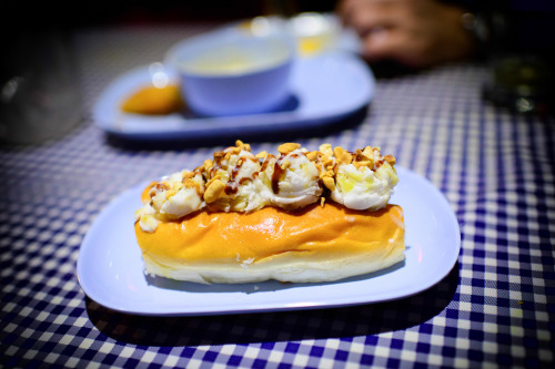 coconut ice cream sandwich in a sweet hot dog bun topped with corn, gingko nuts, nata de coco, palm seeds, crushed cookies, cashews, and sweetened condensed milk photo by alwe