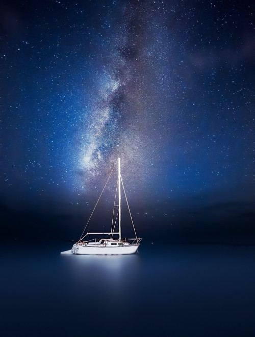 Beautiful photo by Jesse Summers of a boat framed by the Milky Way