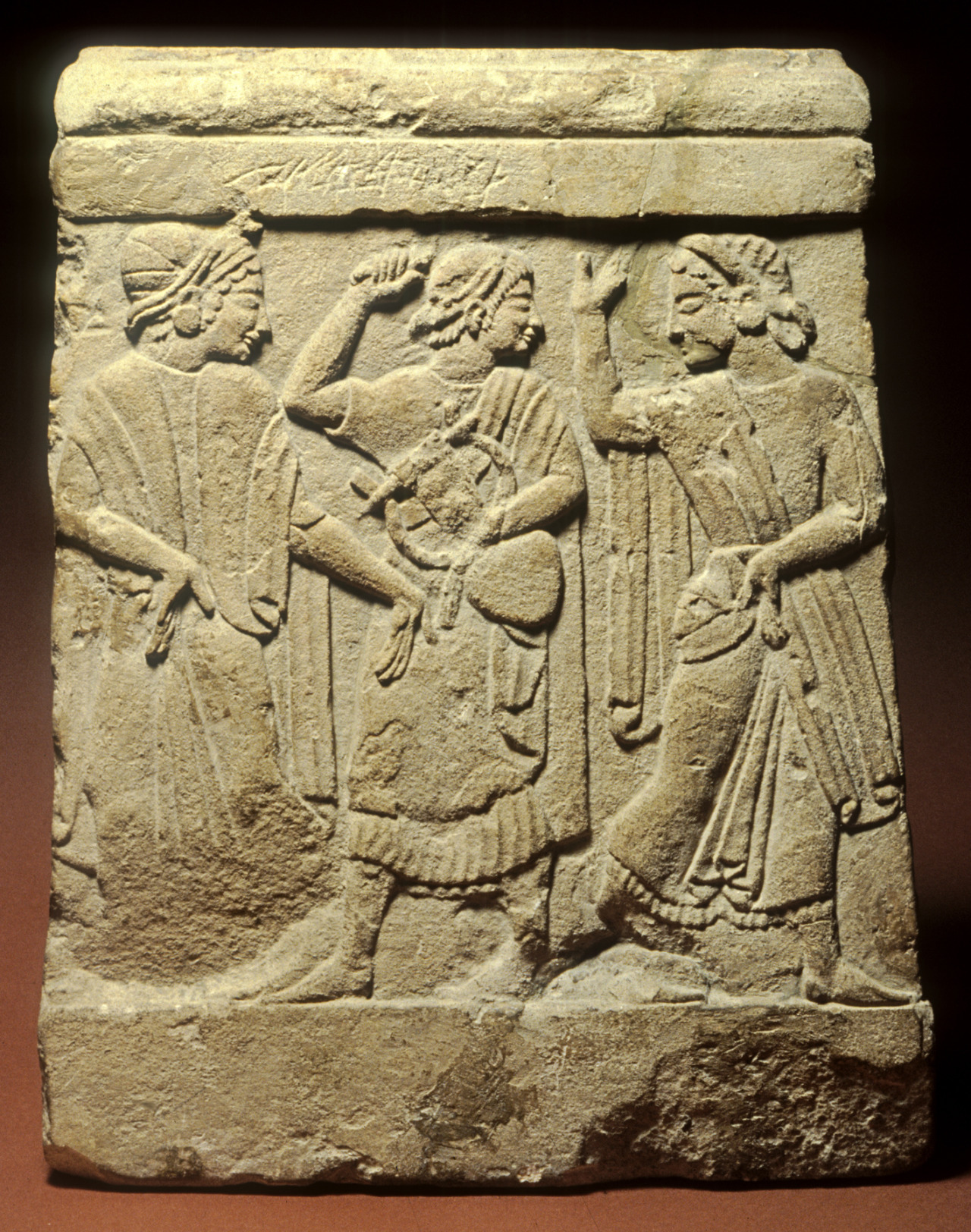 "Relief from a Funerary Cippus, Etruscan, early 5th century BC, made of limestone.  On this relief from a funerary cippus (monument), a man holding a lyre stands between two dancing women. Such pyramidal monuments are typical of the region around Chiusi and depict the dances that took place during the ritual funerary banquet. These reliefs evoke the elaborate wall-paintings of dancers found in such celebrated Etruscan tombs as the ""Tomb of the Leopards"" in Tarquinia and were influenced by contemporary Greek vase-paintings.  Courtesy & currently located at the Walters Art Museum, USA"