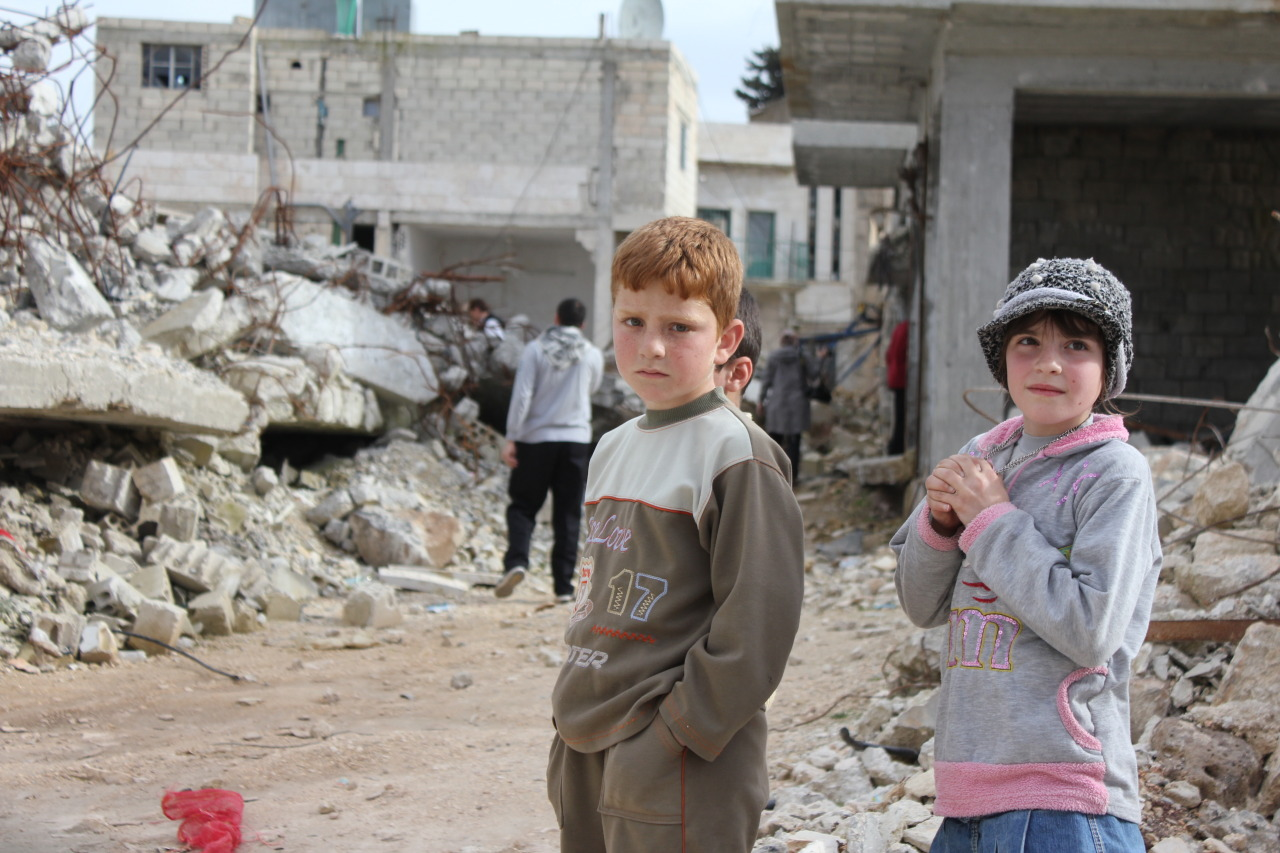 Two children stand near destroyed buildings in their hometown. The girl recently lost her grandfather to a rocket attack by the Syrian Army.