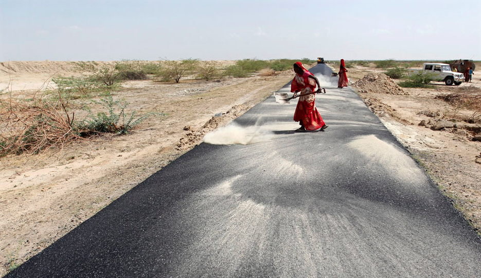 Women labourers throw dust on a road tarmac under construction at Bharadva village in the western Indian state of Gujarat April 23, 2013. India's worst economic slowdown in a decade has bottomed out and growth is expected to pick up to 6.4 percent in the current fiscal year, chairman of the PM's Economic Advisory Council C. Rangarajan said on Tuesday. REUTERS/Amit Dave