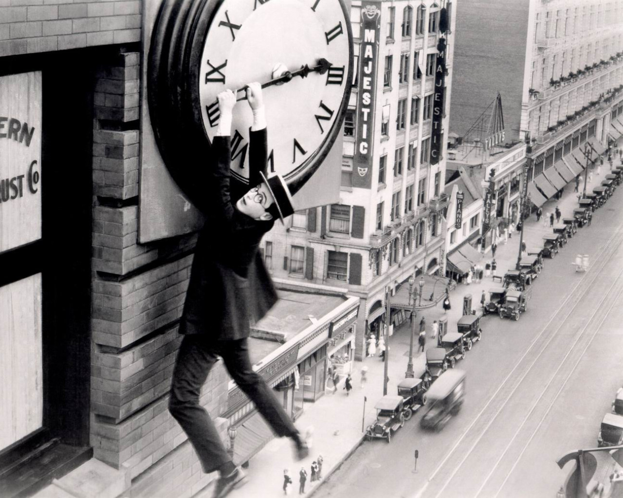acehotel:  Harold Lloyd isn't trying to stop time in this famous scene from the 1923 silent comedy, Safety Last. The reason he's hanging from this clocktower involves a convoluted tale of trying to make good in the big city, impress the true love he left back in Smalltown and make a quick bundle by scaling a 12-story building so that the fictional DeVore Department Store on the ground floor can generate some buzz and ideally move the merch — all that Horatio Alger stuff that doesn't really change quite as much as it stays the same. The minute hand Harold's holding onto over Broadway belongs to what is now the Sparkle Factory, owned by our good friend Tarina Tarantino, and stands across the street from the future Ace Hotel Downtown Los Angeles. The marquee you see in Harry's background is for the former Majestic Theatre. By all accounts, it lived up to its name until it was demolished in 1933. While it's too bad the Majestic couldn't make it to the present in its physical form, we're glad Harold's literal take on social climbing managed to stop the clock and preserve its memory forever.