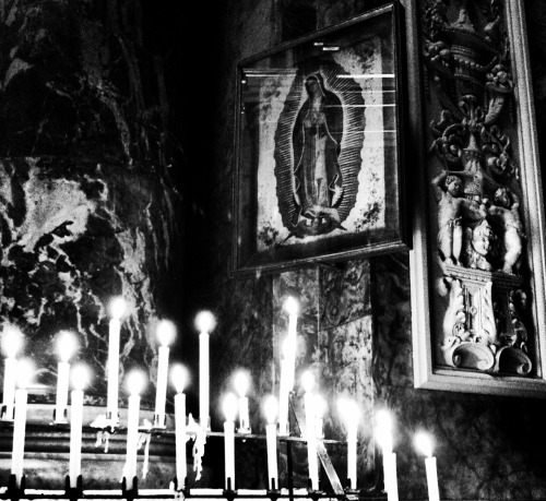 Votive candles burning before an image of Our Lady of Guadalupe in the Brompton Oratory, London.
