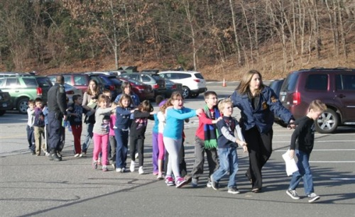 shortformblog:  nbcnews:  Shooting reported at Connecticut elementary school (Photo: Shannon Hicks / The Newtown Bee) State police were responding to reports of a shooting Friday at an elementary school in Newtown, Conn., State Police Lt. Paul Vance told NBC News.  Vance had no information as to possible injuries and no information on the apparent shooter at Sandy Hook Elementary School. The Newtown Bee reported that one child, apparently wounded, was carried from the scene by a police officer. Read the developing story.    Such a terrifying photo. Kids should not have to deal with this, ever.
