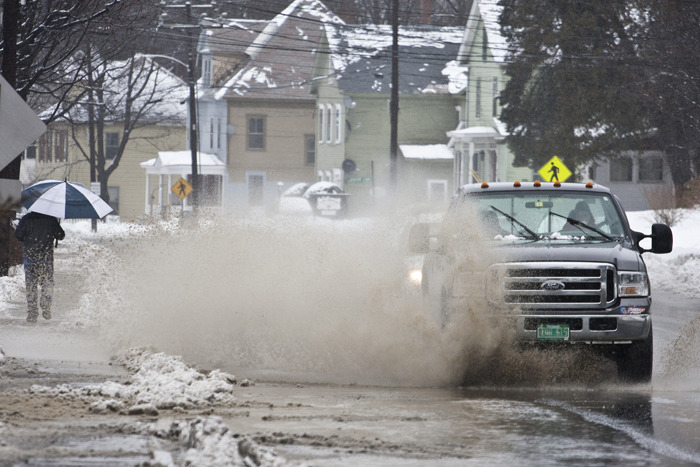 Splash! A truck plows through a large puddle on Western Avenue in Brattleboro, Vt., as rain melts the snow causing flooding in some areas, Wednesday, February 27, 2013. (Zachary P. Stephens/Brattleboro Reformer) Behind the scenes: I drove by this puddle earlier in the day and thought that it might make a good shot to illustrate the nasty weather that we were having. I had some other things to do first so I decided that I would stop on my way back. I parked on the other side of the street and had to navigate my way through the giant puddles without falling in ( I should have brought my floaties). Once I got across I had to play the waiting game. I wanted to get the biggest splash I could and it turns out that I lucked out with getting the mail carrier with the umbrella in the background, which is my favorite part of the shot. Overall I think I shot 4 or 5 different cars going through this puddle. There were a surprising amount that would actually drive around it. The key was to wait for traffic coming from both directions so the cars would be forced into the puddle. I shot this with a Canon 70-200mm f/4L so I could stand a little further away and not get soaked by the cars. Even so, every shot I took I had to quickly jump back into the snow bank as the cars came closer and hit another one of the giant puddles right near me.