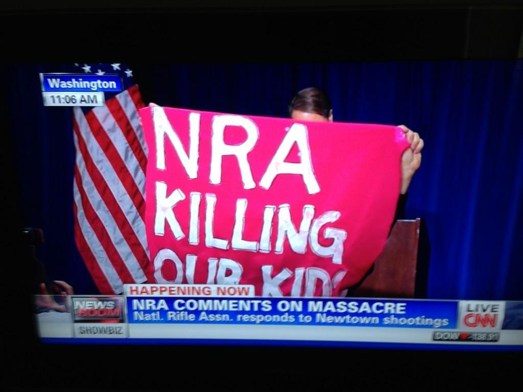 "The NRA press conference was interrupted by a protester holding up this sign and yelling ""The NRA is killing our children."" Watch it live."