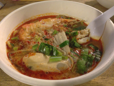 Tom Yum Goong We were wandering though Tarad Rot Fai (the train market) and feeling a bit peckish despite snacking on sai krok isaan and gorgeous shrimp dumplings amid row upon row of goods for sale.   Knockoff Converse sneakers, pop-up clothing shops fashioned from VW vans, vintage motocross gear, industrial lighting - if you a need a certain thing, chances are you'll find that very thing here. It's the ideal place to get slowly drunk on daiquiri-like smoothies, pretend that hot wind blasting your dome is a cool breeze and people watch with the locals. Tom yum goong is apparently a favorite dish among farang, the red-faced foreigners you'll see lurching around at high noon a hair away from a heatstroke. Note to tourists: Poking around Bangkok's many huge, sprawling markets makes more sense after the sun goes down.  As for the 'hot and sour prawn soup', an accurate yet wildly modest description, it simply killed. I should hope once in my life to craft a stock so incredibly rich and nuanced. We stood in a long queque and finally sat down at a crooked wood table next to an overdressed hi-so Pomeranian and his owner.  When my soup arrived, brimming with fat mussels and flecked with roasted chilis, I could feel the jealous eyes of the queque burning a hole in the back of my head.  I'll go again soon and document the exact location 'tho you might find it by looking closely and following the longest line.