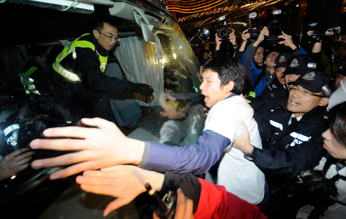 HONG KONG (01/01/13) — A protestor attempts to stop a police vehicle which carries another protester who is arrested by police during a protest against the city's leader Leung Chung-ying in Hong Kong on January 1, 2013. Tens of thousands of protesters took to the streets of Hong Kong on January 1, calling for the city's embattled leader to quit and demanding greater democracy 15 years after it returned to Chinese rule. Photo by Justin Chin