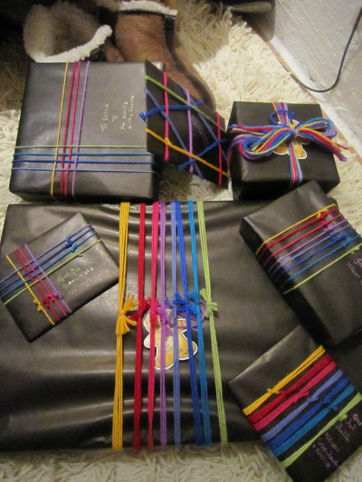 I love gift wrapping. I spend a lot of time each year getting my presents wrapped up so nicely people don't wanna open them! XD Here's how I did it this year. This year I got a bit fed up. Just a little. There were a lot of knots to tie. Also, the strings are woollen and gave me carpet burns.