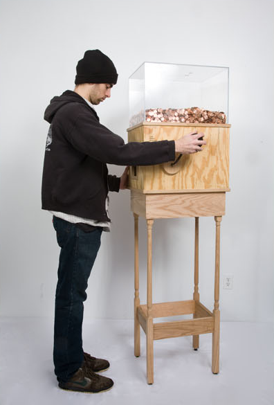 "Blake Fall-Conroy, ""Minimum Wage Machine,"" 2008-2010 This machine allows anyone to work for minimum wage for as long as they like.  Turning the crank on the side releases one penny every 4.97 seconds, for a total of $7.25 per hour.  This corresponds to minimum wage for a person in New York.   This piece is brilliant on multiple levels, particularly as social commentary.  Without a doubt, most people who started operating the machine for fun would quickly grow disheartened and stop when realizing just how little they're earning by turning this mindless crank.  A person would then conceivably realize that this is what nearly two million people in the United States do every day…at much harder jobs than turning a crank.  This turns the piece into a simple, yet effective argument for raising the minimum wage.   Visit his website here."