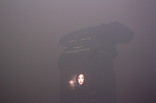 climateadaptation:  kateoplis:  Nope, this is not a still from Blade Runner. It's smog in Beijing.   Some of my friends in Beijing have said the air burns their eyes and lungs. Here's a picture of my colleague with his double-barreled air mask. Intense. Note he's wearing a trash bag to protect his suit from the dirty air when he goes out.  As we pointed out the other day, Beijing hit an extremely high level on the air-quality chart over the weekend. This is scary stuff, guys.