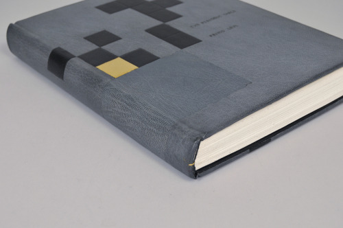 "Look. Look I made a book. And then I took some pictures of it. The design is FLAWLESS. Also HILARIOUS. Supposing you know the book. See, it's called The Periodic Table (it is about a Jewish chemist during World War II) and all the chapters are named after elements. So, the cover is the periodic table with the elements with chapters named after them highlighted. The gold one is gold. The edge is graphite with the chapter titled ""Gold"" gilt. Tragically, while I was surface gilding I dripped stuff on the cover and then it became hideous and so I had to put a patch over it and it is super obvious and embarrassing. Also, it doesn't quite close because one of the doublures doesn't stick to the joint like it ought, and I should have pared it thinner, but I was getting close to the deadline and apparently was too nervous to do good work. But now it is on exhibit, and not very well lit, so you can barely tell!"