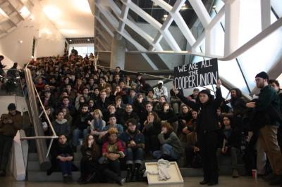 "These are the students, and they are all Cooper Union. They are there to address the Board of Trustees, which ""votes"" today to determine if they end the 100+ years of tuition-free undergraduate education at the school.  The only problem with the fact that the students showed up is that the Board didn't show up. After telling these same students that the Trustees are dedicated to communication and transparency on Friday, the Board has moved the meeting to a secret location, where no one has to meet anyone's eyes. That's character. It may seem to be a tangent, but it's also of note that All the Cooper Union fits in that huge staircase, which has no function except (with three elevators) moving this many students into the tiny classrooms at the edges of the building. The reason there's so much empty space has to do with zoning laws that were designed — in spirit — to prevent a building this large from going up. By keeping a small number of usable square feet, but embedding it in a monstrously large unusable shell, the Trustees and the architects were able to meet the letter of the law (encouraging modest construction) and still find a way to spend $175MM on the building. Coincidentally: it's a building that had part of its construction contract awarded to a family member of the Board of Trustees.  So here is All of the Cooper Union in a staircase atrium: a space deliberately designed to avoid function. But that space found a function today. Or it would have, if only the Trustees had walked the walk and showed up to the building.  After all, they built it."