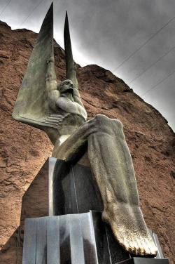"""anyskin:Hoover Dam Angel - Two 30-foot tall bronze sculptures by Oskar Hansen at Hoover Dam are an unusual depiction of male angels. They are part of Hansen's work to memorialize the workers killed during the construction of the dam. """"Winged Figures of the Republic"""" were each formed in a continuous pour. To put such large bronzes into place without marring the highly polished bronze surface, they were placed on ice and guided into position as the ice melted."""