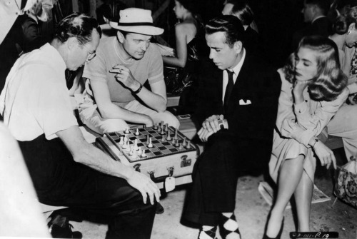 Musician Lew Snowden and Humphrey Bogart play a game of chess on the set of Dead Reckoning. Visitor John Loder and Lizabeth Scott are the spectators.