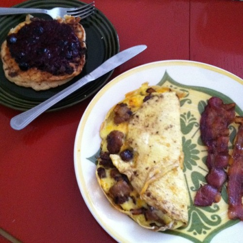 Cheddar and chorizo omelette with bacon and a peanut butter chocolate chip pancake with berry topping #gratuitousfoodpictomakemomjealous