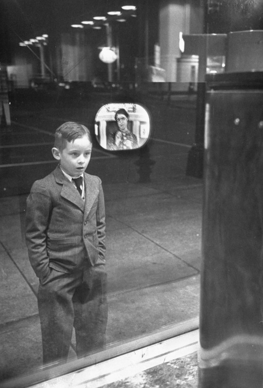 A boy watches TV in an appliance store window, 1948. By Ralph Morse