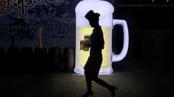 CHOPP. Una camarera pasa junto a un anuncio lleva jarras de cerveza durante la FIesta de la Cerveza Taedonggang en Pyongyang, Corea del Norte. El festival, el primero de su tipo en el país, se llevó a cabo como un evento promocional para cerveza elaborada localmente. (Foto AP / Dita Alangkara)