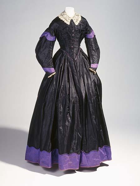 Half-mourning dress, 1855-65 (ca 1860-63?), the North Carolina Museum of History  TWO-PIECE HAND-SEWN, BLACK SILK DRESS, FITTED, LINED, BONED BODICE, PLAIN ROUND NECKLINE, EIGHT PURPLE/BLACK SQUARE DECORATIVE BUTTONS ABOVE HOOK AND EYE CLOSURE AT CENTER FRONT, DROPPED SHOULDER, PURPLE PIPING, SHAPED SLEEVES W/PURPLE CUFFS, LACE BASTED ON CUFF EDGES; UNLINED, BELL-SHAPED, BOX PLEATED SKIRT W/WIDE PURPLE BAND AT HEMLINE (TOP OF BAND IS SINUOUS AND FINISHED W/TWISTED CORDING), LOWER EDGE OF HEM FINISHED W/URPLE WOOL BRAID, SLIGHT TRAIN, UNLINED EXCEPT FOR GLAZED BROWN COTTON AT HEM, PAIRS OF NARROW, BRAIDED TIES AT INSIDE SEAMLINES NEAR HEM, HOOK AND EYE ON WAISTBAND.