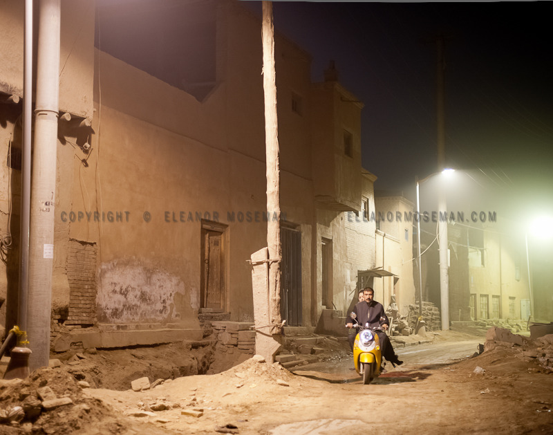 "A Uyghur couple rides an electric scooter through Old Town, Kashgar. This part of Kashgar is being demolished and rebuilt like many ""ancient"" towns in China. It will soon be ""jiade"" like the Great Wall and so many other ""new"" old and ancient places. I was there last March and again in August and couldn't believe what had happened in such a short period of time.  Kashgar, October 2012 www.wandercyclist.com"