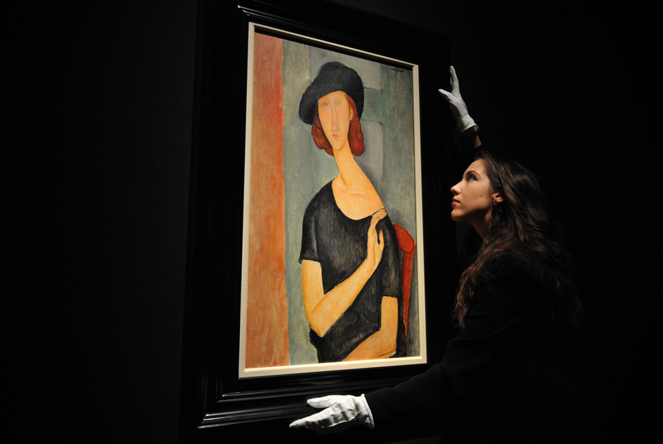 "A member of staff poses next to a work entitled ""Jeanne Hebuterne (au chapeau)' by Italian artist Amedeo Modigliani at Christie's auction house in central London."