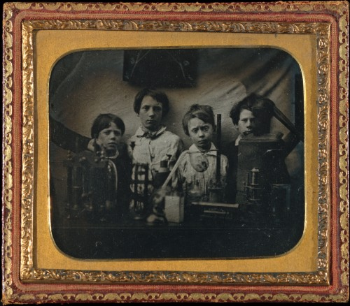 "ca. 1850's, [daguerreotype portrait of four nonplussed boys posed behind science and lab equipment; photo backed with a printed entrance ticket for ""Severn Street British School Christmas Tea Meeting""] via the Metropolitan Museum of Art, Photography Collection"