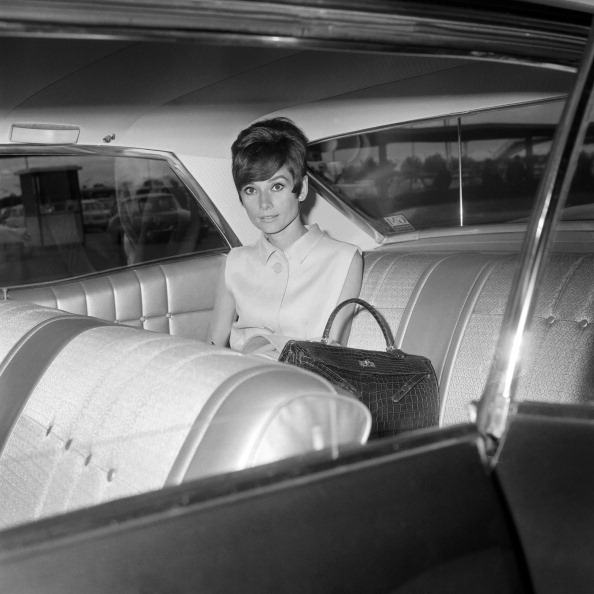 "The actress Audrey Hepburn photographed into her car, arriving at the Orly Airport in Paris (France), on August 23, 1965. -Audrey was wearing dress of Givenchy (of his collection for the Spring/Summer of 1965),  Note: Next to Audrey her handbag of Hermès (model ""Kelly"")."