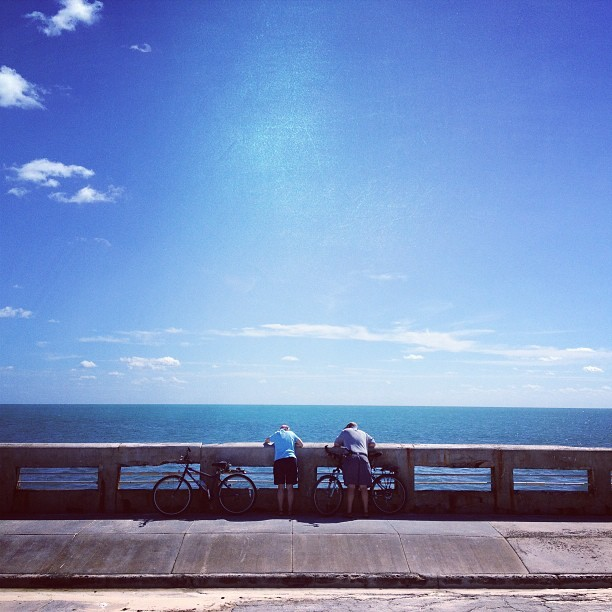 An old couple peers into the great blue in #keywest #florida #ocean #cycling #love (at White Street Pier)