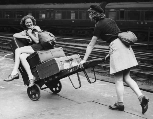 Two holidaymakers amuse themselves with a porter's trolley as they wait for their train at Euston Station in London in August 1939. (via The Ways We Wait: A Train Station Tribute For Grand Central's 100th : The Picture Show : NPR)