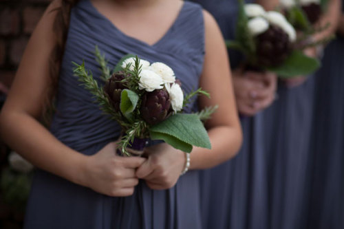 Bridesmaid bouquets of white ranunculus blossoms with artichoke, rosemary, and hydrangea leaves, wrapped in thick twine for a natural rustic touch. Image by Castaldo Studios