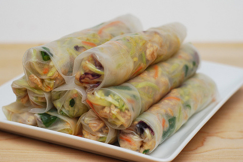 prettygirlfood:  Pork Spring Rolls 1/4 cup hoisin sauce 1/4 cup soy sauce 2 tablespoons Asian chili-garlic sauce (or to taste; optional) 1/4 cup water 1 (16oz) bag coleslaw mix 1/2 cup chopped fresh cilantro 6 scallions/green onions, white parts minced; green parts sliced thin 1 tablespoon vegetable oil 1 pound ground pork 3 tablespoons freshly grated ginger 12 (9 inch) rice paper wrappers Combine the hoisin, soy, and chili garlic sauces and water in a small bowl. In another bowl, combine the coleslaw, cilantro and scallion greens; set aside. Heat oil in a large skillet over medium high heat until just smoking. Add pork and 1/3 cup of the hoisin sauce mixture. (The remaining hoisin sauce will be used as a condiment for dipping.) Cook the pork until no longer pink, about 5 minutes. Stir in the ginger and scallion whites and cook until fragrant. Place this pork mixture into the bowl with the coleslaw, cilantro and scallion greens. Toss to combine. Spread a clean, damp kitchen towel on the counter. Soak a rice paper wrapper in a shallow bowl of warm water, about 10 seconds, and spread out on towel. Arrange 1/2 cup of filling on each wrapper, leaving a 2 inch border on the bottom. Fold in sides and roll up tightly like a burrito. Repeat with remaining wrappers and filling. Serve with the remaining hoisin sauce mixture for dipping.