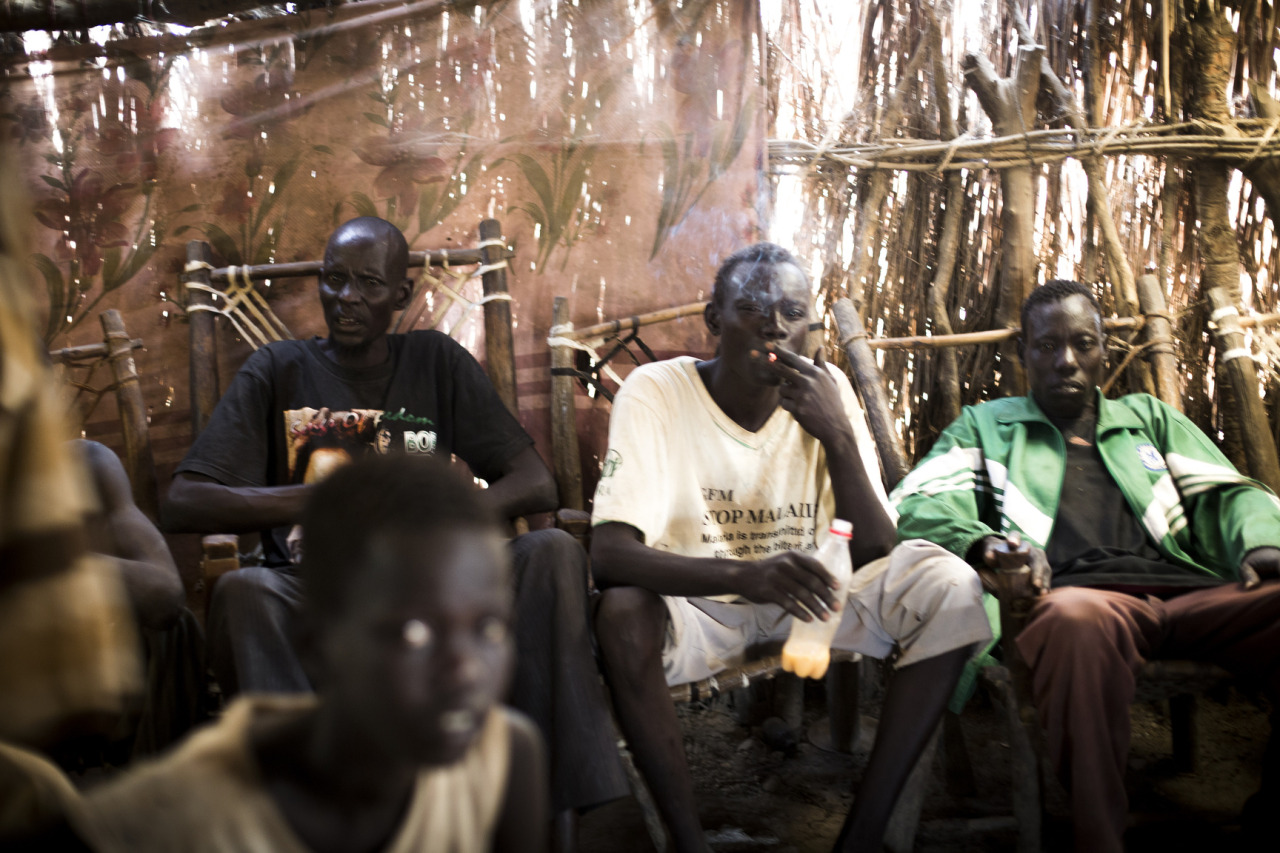 In a local bar in Turalei, South Sudan, internally displaced South Sudanese and returnees from Khartoum are under influence of home-made beer made of sorghum from the early hours of the morning. Most came back after the Independence of South Sudan in 2011, but very few manage to find a job or make a living. They are badly hit by food shortage and struggle to adapt themselves into a society they do not belong to. © Camille Lepage - All rights reserved 2013