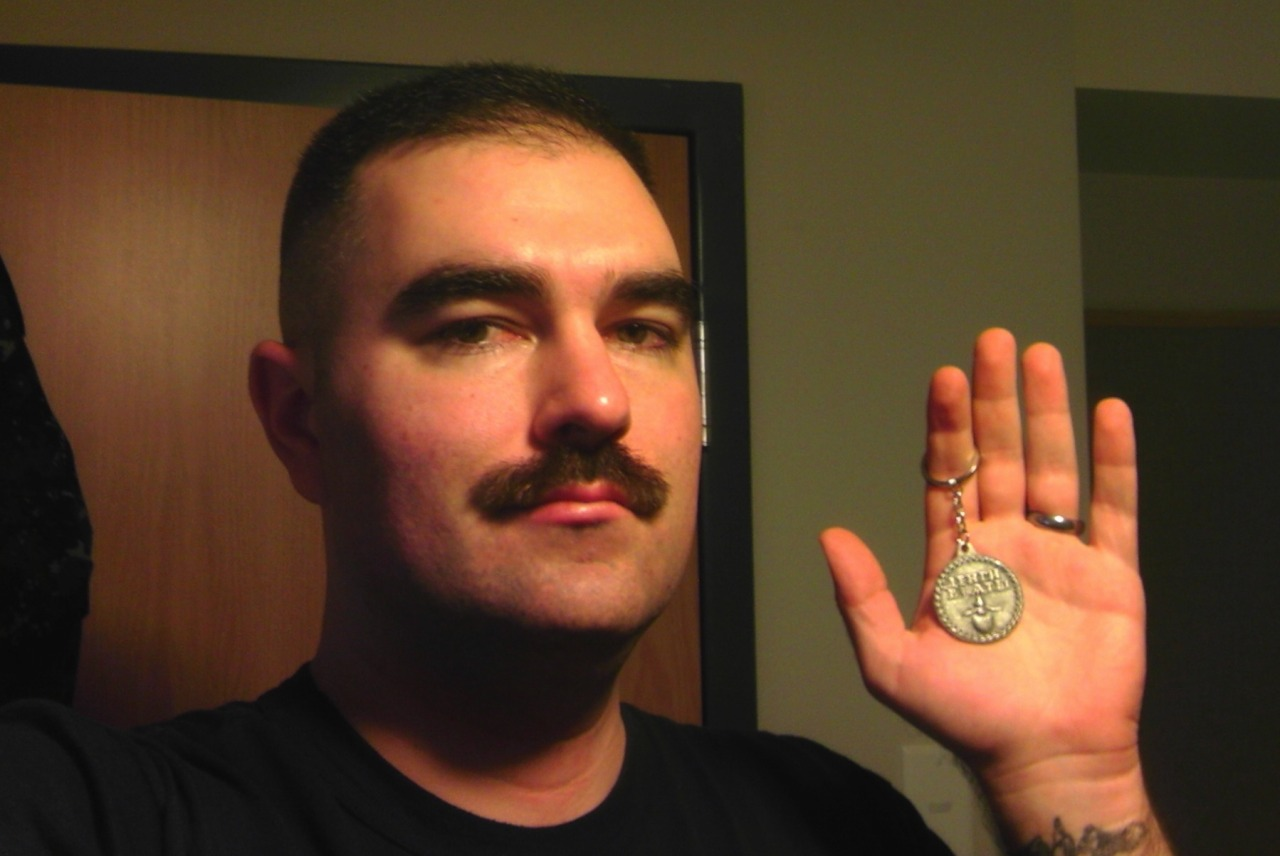"This is Donovan Hixson with his Beard Token. He wrote, ""I don't have a beard because I'm in the US Navy, a Chief Petty Officer, and the uniform regulations permit a mustache as the only facial allowed."" I'm glad Donovan sent this in, because guys with mustaches write in asking if they would be included because it is a ""Beard"" Token, but when Peter the Great enforced the Beard Tax, it was levied on all styles of facial hair, including mustaches. If you rocked a mustache in 1705 Russia, you had to carry a Beard Token, otherwise you risked some official shaving it with a dull razor, or in some instances plucking it out one hair at a time, at least according to folklore."