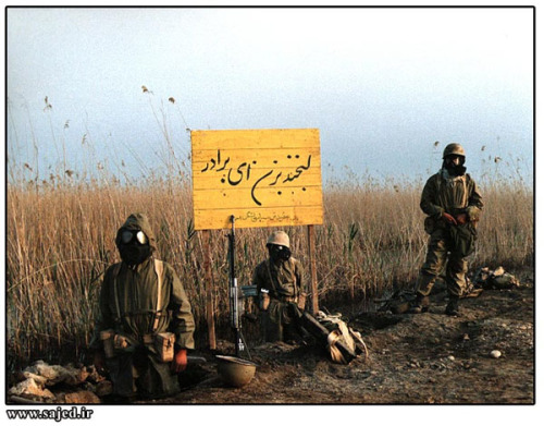 "Iranian Soldiers in NBC Suits in the front line of Iran-Iraq War. (Circa 1980's)  The Sign in the middle says ""Oh Brother, Smile"" In Persian."