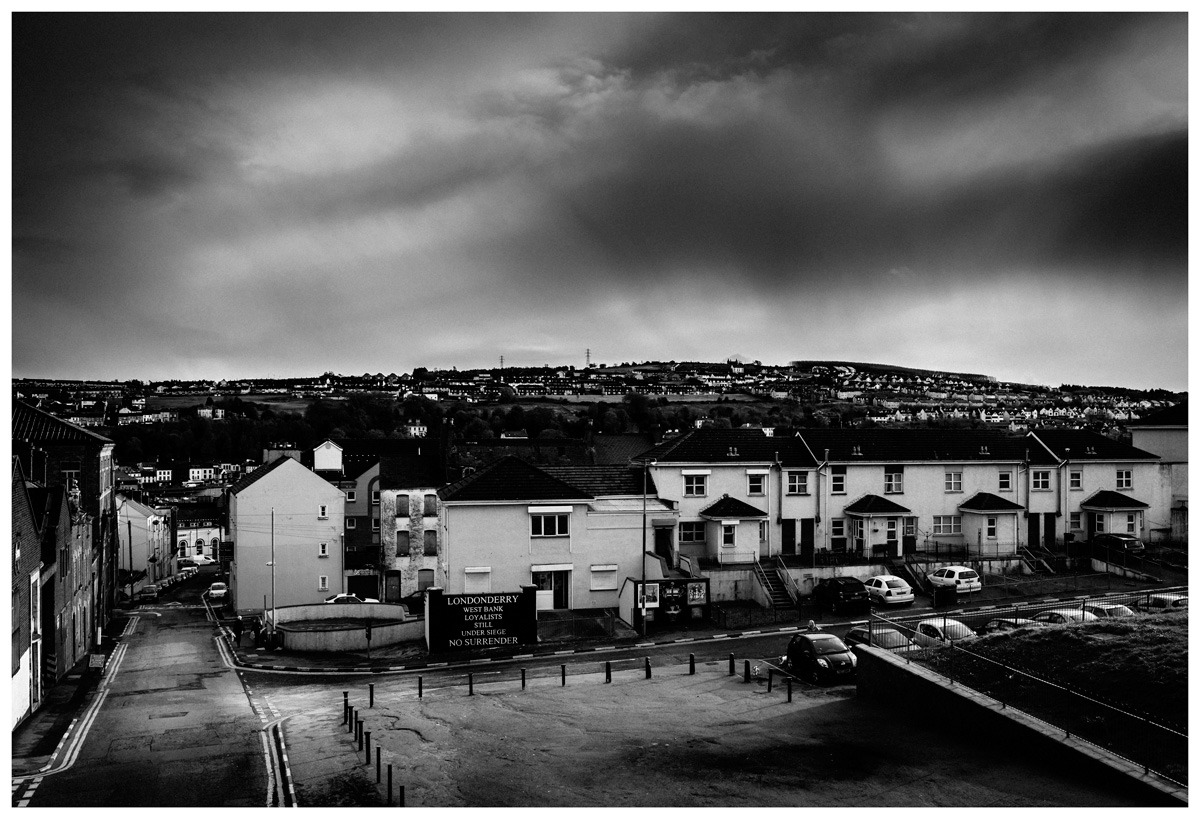 West Bank Loyalist Housing Area, Londonderry/Derry While I was in Derry, I had an opportunity to walk around and photograph some of the parts of the city that remain visually strident. My memories of the troubles, as reported to me in the UK when they were at their peak came from this city, and I was staggered at how small the place is. Here, an enclave of loyalist supporters live within a mainly republican area. The arriving storm in the sky added a certain doggedness to the scene. Photo: Andrew Shaylor Note:I have received a correction from #UK Justice Forum. They have informed me that my description was incorrect. They say 'you are wrong in your description. It is called the Fountain Estate and it is Protestant - not entirely Loyalist'.