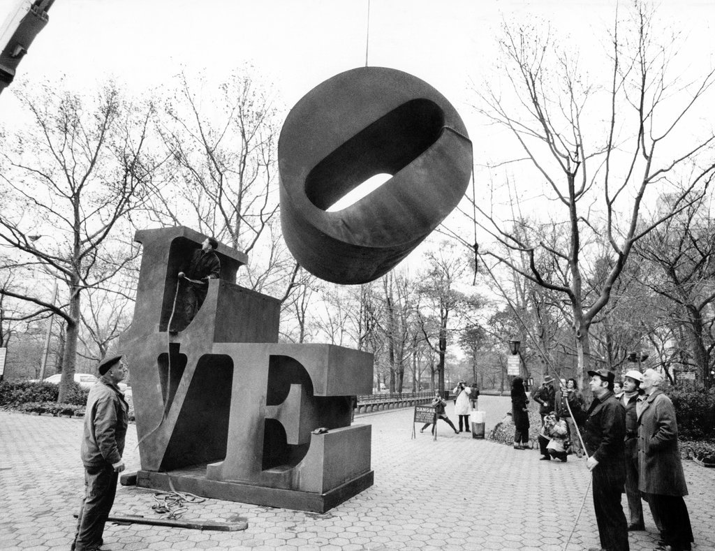 "Nov. 29, 1971: In time for the holidays, the O of the famous ""Love"" sculpture, by Robert Indiana, was lowered into place — at Fifth Avenue and 60th Street — on a cold day that foreshadowed rain. Photo: Don Hogan Charles/The New York Times"