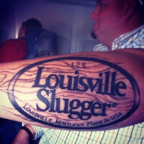 Bad Tattoo of the Week: Opening Day Edition Could this Louisville Slugger tattoo be the worst baseball tattoo ever? Perhaps. It's quality work but who the hell wants their arm to look like a baseball bat or be a walking endorsement for a company. I'm hoping this guy did this as a way to get bats for life or a fat check from Louisville Slugger. My guess is he did because he's a big dummy.