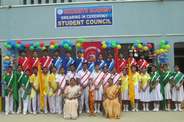 "Swearing ceremony of the student Council The new student council was installed at Nazareth Academy, Gaya, during a special ceremony on April 16. From the chapel with a lit lamp, the newly elected leaders went in procession for the school assembly. One by one, they lit their candles from the lamp and placed them on two decorated stands.  The lamp symbolized Christ, the source of all light, who would guide them in their new role as leaders. Principal Sophia Joseph, SCN, Vice Principal Seema Monippallikalayil, SCN, and teachers pinned the leadership badges on each student council member. The leaders made a solemn promise that they would perform their duties, carry out their responsibilities faithfully, and become the ideal students that they would like to be.  The Oath ceremony concluded with the school song, ""Jesus of Nazareth who loves us all … when we proudly call Nazareth Academy."""