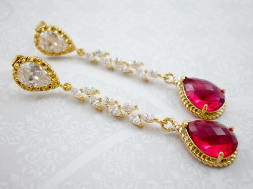 Stunning ruby red glass pendants in a faceted teardrop are complimented by a gold plate setting with rope detail. Cubic zirconia cascading leaves join the ruby red pendant to beautiful earring posts. The earring posts are crystal with gold plate over sterling silver.