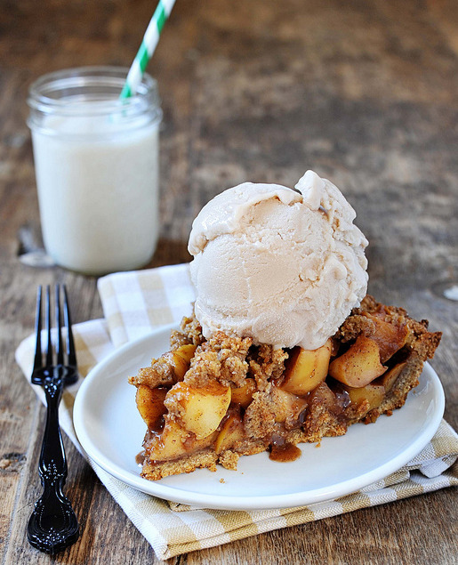 """caramel crumble apple pie in whole wheat pecan crust with homemade vanilla ice cream, milk in mason jar in the back."""
