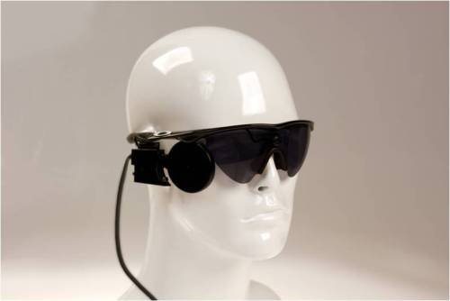 "First Bionic Eye For US Market Awaits Approval From FDA     The retina is the back part of your eye with the cells that respond to light. The cells are known as photo receptors and come in two varieties: rods and cones. Rods are very sensitive to light, shapes and movements and cones are not as sensitive, but they control the perception of color.      Like a digital camera, the retina does basic optical processing like edge detection and enhancement and color separation. It transmits images through the optical nerve and then your brain returns the inverted image to its correct right side up. People with retinitis pigmentosa (RP), can't do that. RP is an inherited eye disease – it causes retinal degeneration which means a gradual decline in vision and eventually blindness. It's also considered an orphan disease which means not enough people have it to warrant a bevy of researchers, scientists and pharmaceutical lobbyists to devote entire and massive budgets to its cure. Last week, the Federal Drug Administration (FDA) was supposed to approve Second Sight's Argus® II Retinal Prosthesis System, for use in the United States. If the approval comes, it will signal more than 20 years of work in the field, two clinical trials, more than $100M in public investment by the National Eye Institute, the Department of Energy, and the National Science Foundation, and an additional $100M in private investments. Not to mention it will be the first bionic eye available in the US Market. The Argus II was approved with the CE mark for use in Europe in 2011 and the Retinal Prosthesis system is the first prosthesis of its kind in the world. Think part Six Million Dollar Man where the tech was all in Steve Austin's eye and part Geordi La Forge from Star Trek, where the ""glasses"" helped him see, the Argus II takes us farther down the road of using bio-electronics and understanding how our body works and uses electronic pulses. In the case of the Argus II, the bionic eye or more accurately, the artificial retina, will turn darkness into light through a system comprised of electronics in the eye and wearable technology which wirelessly transmits a signal to the implant in the eye that lets the patient see again. ""No one really thought it would be possible because the tissue around the eye is so soft and delicate,"" adds Mark Humayun, MD, PhD, Cornelius Pings Professor of Biomedical Engineering and Professor of Ophthalmology, Biomedical Engineering, Cell and Neurobiology, Keck School of Medicine of USC and USC Viterbi School of Engineering, University of Southern California. ""If we continue to develop this type of technology and begin to understand the new electrical language of pulses to the brain, to the eye, we can apply it to other parts of the body and we can change our world and how we relate to it."" Dr. Humayun has been working on this project for 25 years. It may sound idealistic, but ever since he watched his grandmother go blind from Diabetes, he wanted to do something that would help people see again. ""It's amazing to see the ability of the human brain to take low resolution images and make so much of it""  – Dr. Mark Humayun, Professor of Opthalmology and Biomedical Enginering, USC. There are two parts to the Argus II Retinal System. First the implant through surgery. The surgery is not unlike many eye surgeries today but in this case, a trained surgeon will implant the electronics underneath the skin of the eye, known as the conjunctiva. Under anaesthesia, the surgeon will open up the skin of your eye and slide in the electronics of the Argus II  and suture that to your eye . He will then remove the gel-like substance around you eye, called the vitirous, and then slide in saran-wrap like electrodes that make contact with the neural tissue of your retina. Once the electrodes are in place or position, a little micro-tac (the size of two human hairs) will be used to attach to the retina in the eye. Recovery time is about a week, with little pain or discomfort. Then, the technology. Video images captured by a miniature camera inside the patient's glasses into a series of small electrical pulses transmitted wirelessly to an array of electrodes on the surface of the retina inside the eye. These pulses are intended to stimulate the retina's remaining cells resulting in the corresponding perception of patterns of light in the brain. The patient then has to learn to interpret these visual patterns thereby regaining some visual function. And here is the sci-fi part, they don't activate the system right away after the surgery. That's only done when you put on the glasses and a computer system custom fits the patient to set parameters in the wearable tech aka the glasses, each patient is different. Because the glasses have a camera that's encoded to talk wirelessly to the implant, it can send siganls to the implant and the implant decodes them (like morse code). The battery power is all in the glassses in the wearable tech, not the implant. Dr. Humayun, who is also the co-inventor and lead clinical advisor for the Argus II, says this is just a jumping off point. ""Software upgrades will allow us to do more for people – because the implants don't need to change, the glasses can be enhanced with software upgrades,"" adds Dr. Humayun. ""Software upgrades that allow you have a digital zoom, think of your iPhone with the zoom feature – now it would be possible to do that with your eye."" Dr. Humayun adds, ""Also color vision — being able to see more colours naturally. Because each color has a frequency, red, green, yellow, we can learn the frequency of each color and write a software program for that and upload to the glasses and enrich the visual experience."" Although the resulting vision is not the same as when these patients had normal vision, it still provides them a new vision that they did not have before. ""The fact that many patients can use the Argus implant in their activities of daily living such as recognizing large letters, locating the position of objects, and more, the promise to the patients is real and we expect it only to improve over time,"" adds Dr. Humayun. When the Argus II gets approval from the FDA, it will be available later this year in clinical centers across the country."