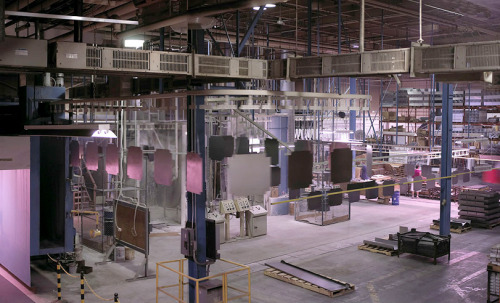Large panels enter a production powder coating oven for baking