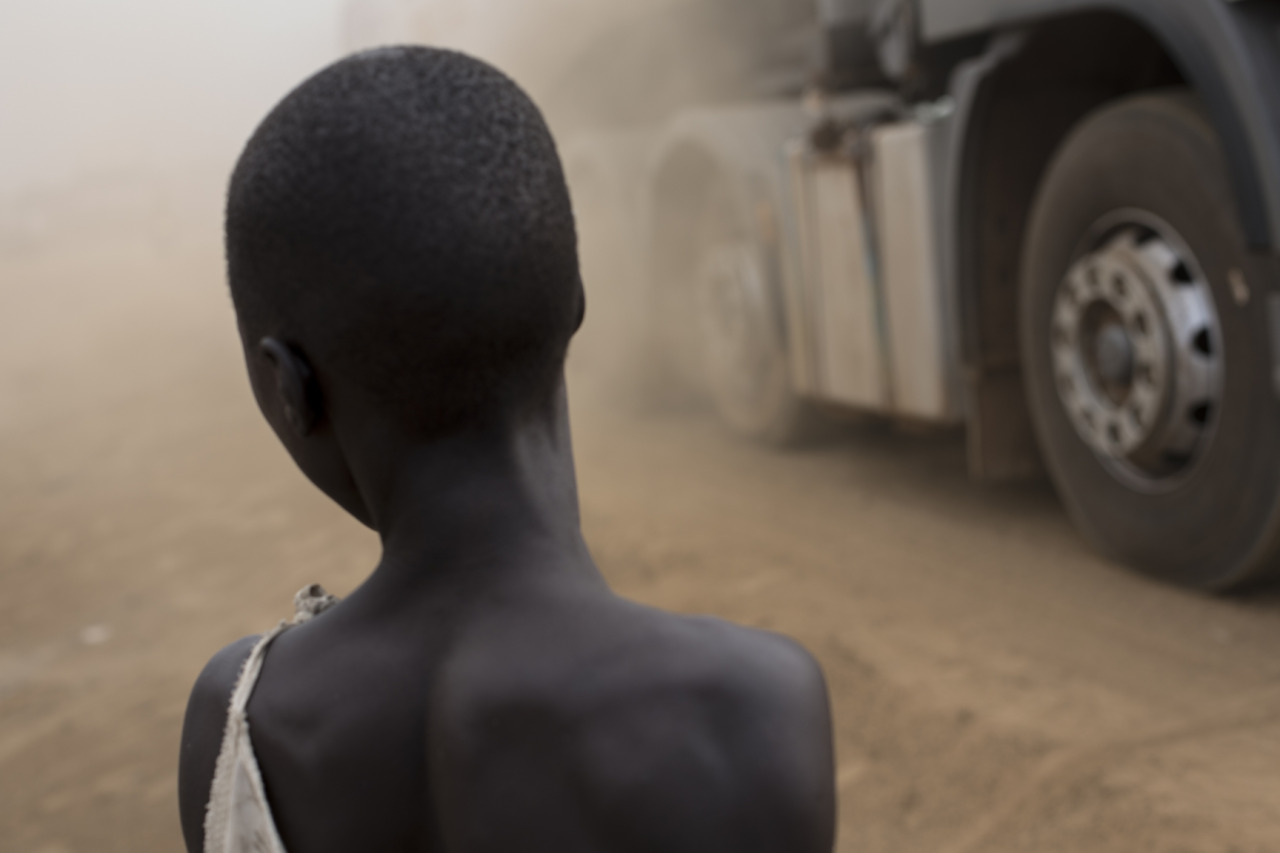 intamunu:  A young girl is getting dust on her face as a truck drives pass her in Nimule, South Sudan on February 19, 2013.  Nimule is the biggest custom place in the country. Despite huge natural resources, South Sudan must import most of it goods from neighbouring countries, such as Kenya and Uganda because there is very little investments in agricultural policy. As a consequence, prices in South Sudan are very high in comparison to other under-developed and developing countries.  © Camille Lepage - All rights reserved 2013
