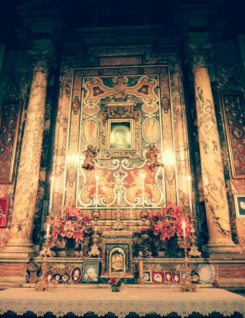 The altar of the Madonna del Pozzo (Our Lady of the Well) in the church of Santa Maria in Via, Rome. The small image of Mary came to light after the overflowing of a well during the night of 26 and 27 September 1256. Pope Alexander IV had a chapel built in honour of this miraculous event. The current chapel dates from 1591 and is located to the right of the entrance to the church. Water continues to flow from the well, which is distributed to visitors in small cups and bottles. The shrine is sometimes referred to as 'la piccola Lourdes', or little Lourdes. The church of Santa Maria in Via is located close to the Via del Corso, one of Rome's main shopping streets. It is common for shoppers to pop into the chapel to drink a cup of miraculous water and for a moment of prayer before the Madonna. It is one of those places where the love of the Roman people for Mary really becomes apparent; men and women of all ages find joy and comfort in the small miraculous image of Our Lady of the Well.