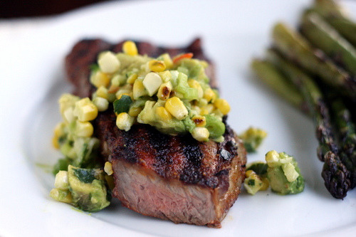 misstressmay:  NY Strip Steaks with Grilled Corn and Avocado Salsa For the salsa: 1 ear of sweet corn 1 clove garlic, minced 1 ripe avocado, cubed 2 Tbsp cilantro, chopped 2 green onions, thinly sliced 1/2 large jalapeno, seeded and chopped 1 1/2 Tbsp lime juice Salt Fresh ground black pepper For the steaks: 2 NY strip steaks, at room temperature for 20-30 minutes Olive oil 1/2 tsp paprika 1/4 tsp chili powder 1/4 tsp garlic powder 1/8 tsp ground cumin 1/4 tsp salt 1/4 tsp fresh ground black pepper Soak the ear of corn in cool water for 15-20 minutes. Pat dry. Heat the grill to medium heat. Grill the corn in the husks, rotating 1/4-turn every 5 minutes until the husks are completely browned. Allow the corn to cool. Cut the kernels off of the cob and place in a medium bowl. Add garlic, avocado, cilantro, jalapeno, green onions, lime juice, and toss to coat. Salt and pepper to taste. Turn grill to high. Brush both sides of steak with olive oil. Combine rub ingredients in a small bowl and mix thoroughly. Coat the steaks with the rub. Grill until cooked to desired doneness, turning once half-way through (about 8 minutes total for ~11oz steaks at medium). Remove from the grill and let stand for 5 minutes. Top with salsa and serve.