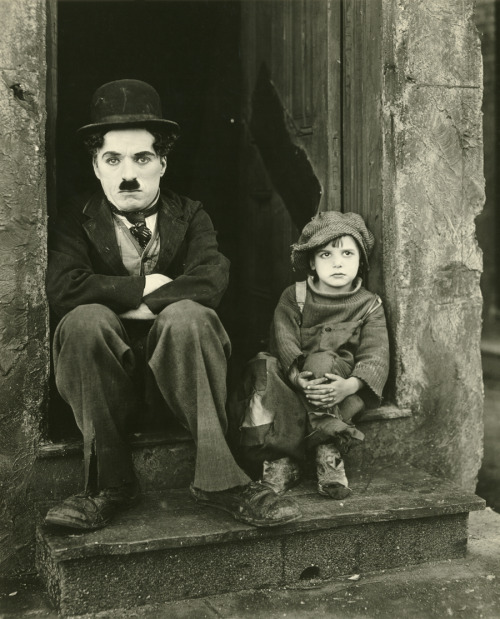 "fewthistle:  Charlie Chaplin and Jackie Coogan in The Kid, 1921. ""The trouble with you, dear, is that you think an angel of the Lord as a creature with wings, whereas he is probably a scruffy little man with a bowler hat.""                              ~Josephine Tey,  The Franchise Affair  (image source: chaplinalife.com)"