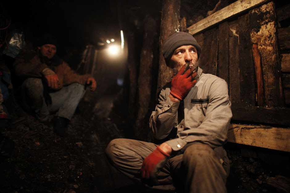 An illegal miner smokes a cigarette during a break from digging at coal mine in the village of Stranjani, near Zenica, December 11, 2012. There are about 20 illegal mines in the area, where Bosnians dig for coal with their bare hands and use makeshift tools, such as bathtubs, to transport the coal. One bag of their coal is sold for 3 euros ($4 dollars), which is popular with the locals as it is cheaper than the coal sold at the city mine. [Credit : Dado Ruvic/Reuters]