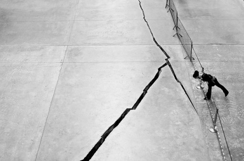 "Don't fall in by Meg Pickard on Flickr.Doris Salcedo's Shibboleth at the Tate Modern ""asks questions about the interaction of sculpture and space, about architecture and the values it enshrines, and about the shaky ideological foundations on which Western notions of modernity are built. In particular, Salcedo is addressing a long legacy of racism and colonialism that underlies the modern world."" Due to a bunch of people falling into the gash (though IMHO you'd have to be trying quite hard to get anything stuck in there) they've now put up a safety barrier. There's probably a deep sociological point to be made there, about people being prevented from hurting themselves on artistic points about racial schism. But I can't summon it. Mind the gap."