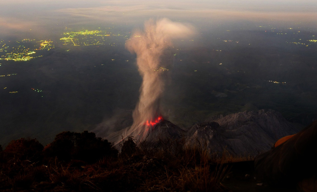 "From 2012: The Year in Volcanic Activity, one of 39 photos. On March 11, 2012, photographer Andrew Hall captured this fantastic image of Santiaguito, an active lava dome on Guatemala's Santa María Volcano. Hall: ""In the middle of the night, restless in my tent after hiking to the top of Volcan Santa Maria with Quetzaltrekkers, I trudged over to the other side of the summit, wrapped myself in my sleeping bag to fight off the chill at 12,000 feet, and watched alone as Volcan Santiaguito erupted again and again over the hours leading up to sunrise. The town of Retalhuleu, just beginning to awake, lies roughly 15 mi beyond."" (© Andrew Hall)"